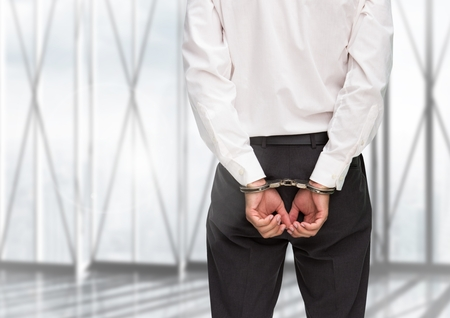 Rear view of guilty businessman with his hands cuffed against window in background Stock Photo