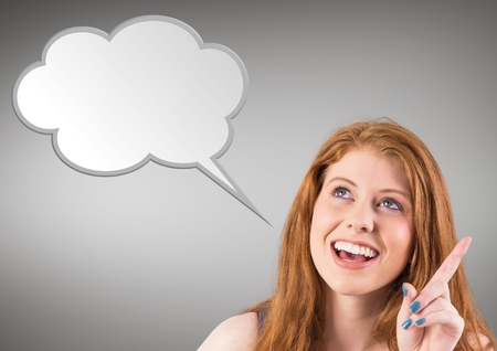 Digitally composite image of smiling woman with blank speech bubble against grey background Stock Photo