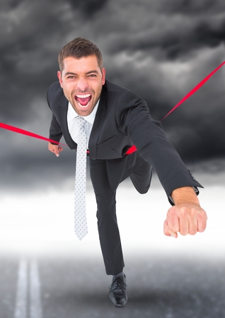 Composite image of excited businessman celebrating at finish line against stormy sky in background