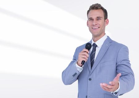Imagen compuesta del hombre de negocios que habla en público en el micrófono contra el fondo blanco