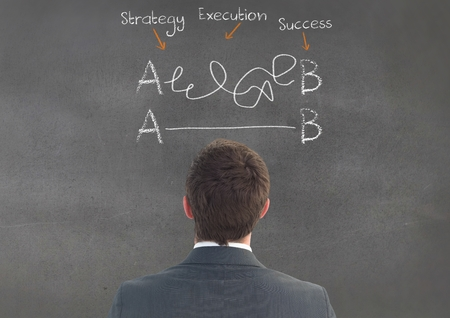 squiggles: Digitally composite image of businessman looking at business terms on chalkboard