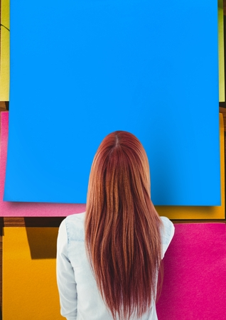 Composite image of woman looking at large blue sticky note Stock Photo