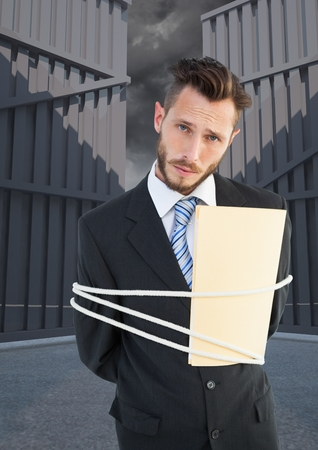 Digital composite image of serious businessman tied up with rope and folder Imagens