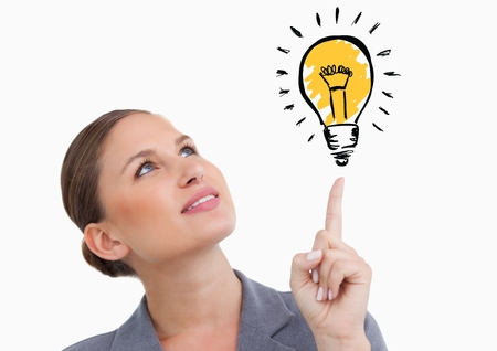 Digital composite image of woman looking at graphic light bulb Stock Photo
