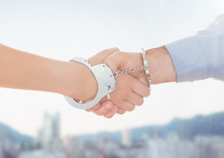 handcuffed: Composite image of handcuffed business people shaking hands