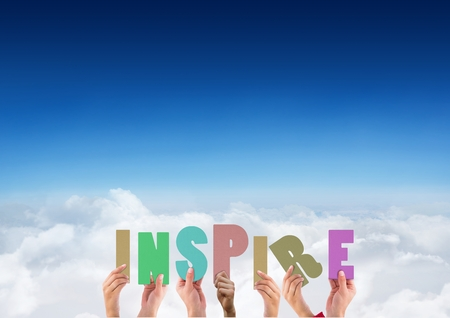 handholding: Digitally composite image of hands holding word INSPIRE against blue sky and clouds