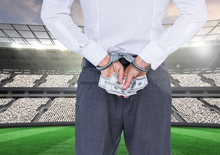 handcuffs: Digitally composite image of corrupt businessman in handcuffs holding money at stadium