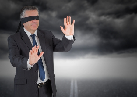 Digitally composite image of businessman in blindfold against storm cloud Stock Photo