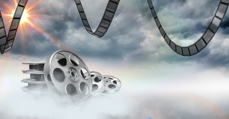 Digital composition of film reels against sky in background