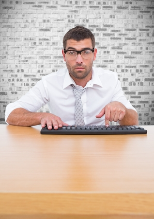 Portrait of man in spectacles typing on keyboard against brick wall background