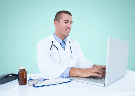 Doctor smiling while using laptop against blue background