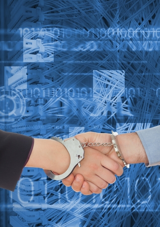 handcuffs: Digital composition of business professionals shaking hands in handcuffs against coding background Stock Photo