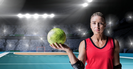 Digital composition of athlete holding  handball against stadium in background Stock Photo