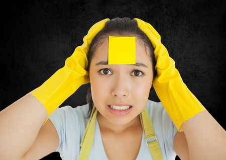 handholding: Stressed cleaner with sticky note stuck o her face against black background