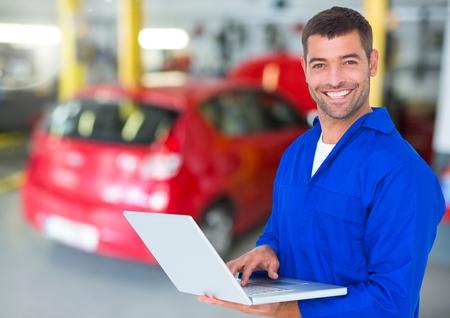 handholding: Mechanic smiling while using laptop in garage