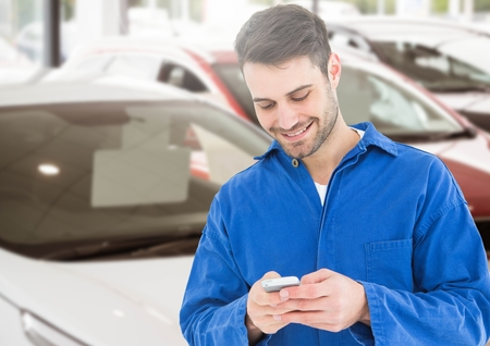 Mechanic smiling while using mobile phone in parking lot