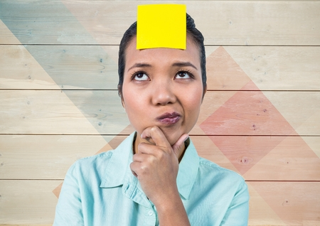 handholding: Digital composition of frustrated woman with sticky note stuck on her head against wooden background
