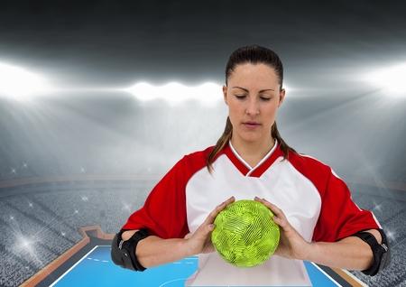 boca cerrada: composición digital de balonmano atleta que sostiene contra el estadio de fondo Foto de archivo