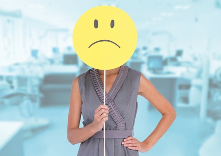 Digital composition of businesswoman  holding sad smiley face in front of her face against office in background