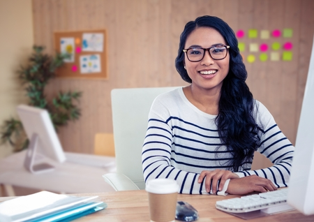 Portrait of woman in spectacles sitting on her desk at office Stock Photo
