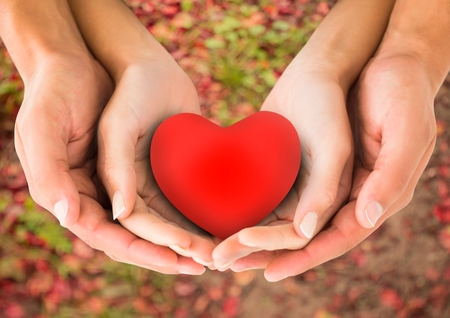 handholding: Close-up of couple hands holding red heart