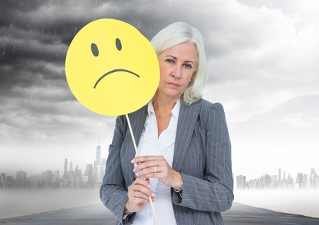 dreariness: Digital composition of businesswoman holding a sad face in front of her face with rain clouds in background