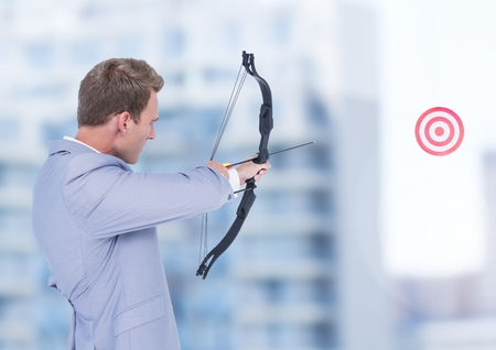 Digital composition of businessman aiming bow and arrow at target Stock Photo