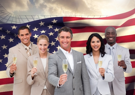 handholding: Portrait of group of happy businesspeople holding champagne flutes against American flag Stock Photo