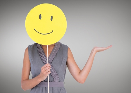 Woman holding a smiley face over her face against grey background