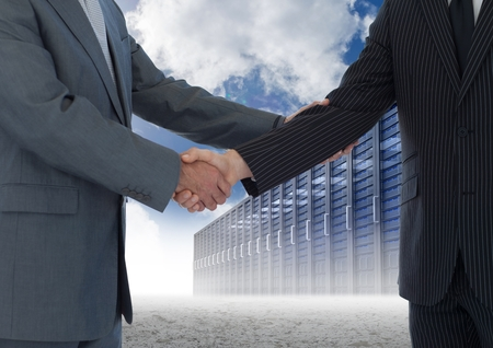 Digital composition of businessman shaking hands with each other and servers against sky in background photo