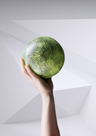 Digital composition of hand holding ball against white background Stock Photo