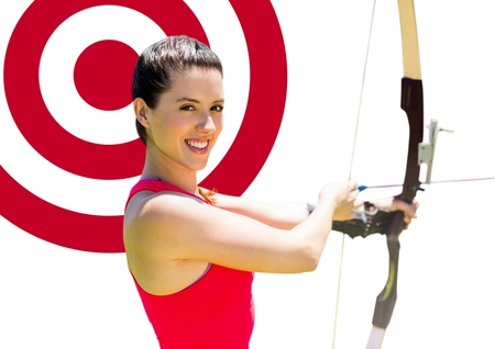 Portrait of woman aiming with bow and arrow at target against white background