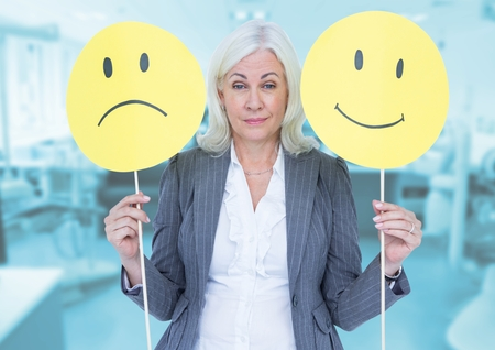 Digital composition of a businesswoman holding smiley and sad faces