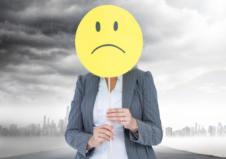 dreariness: Digital composition of businesswoman holding a smiley face in front of her face with rain clouds in background Stock Photo