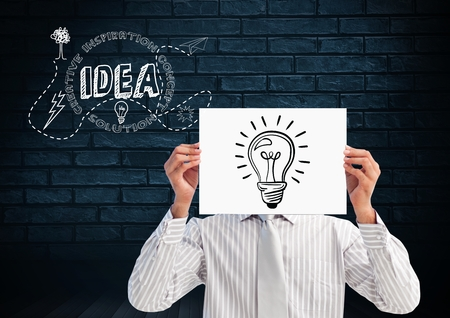 handholding: Digital composition of man holding sheet of paper with drawn light bulb in front of his face and text idea in background