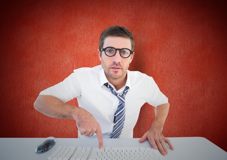 Portrait of a confused man pointing to computer keyboard at desk Stock Photo