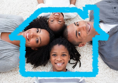 Digital composition of happy family lying on rug overlaid with house shape photo