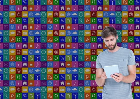 Digital composition of man using digital tablet with various icons in background Stock Photo