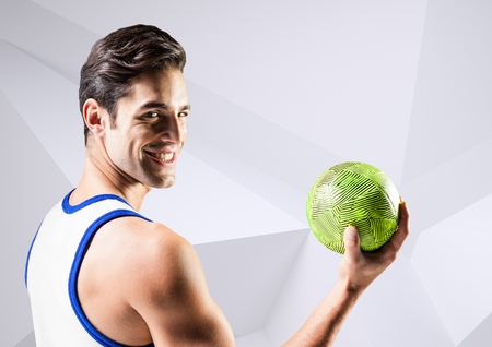 Digital composition of handsome man holding handball against white background Stock Photo
