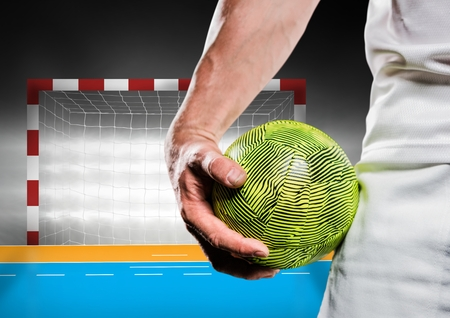 Digital composition of male handball player holding ball against goal post