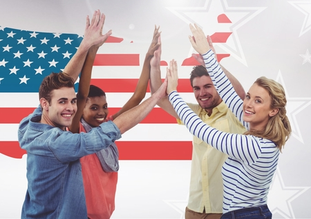 Digital composite image of colleagues giving hi-five to each other against USA flag in background