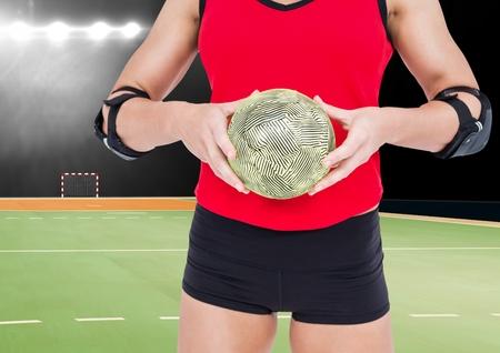 Mid-section of female athlete holding handball against stadium in background
