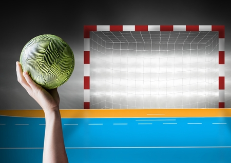 Digital composition of hand holding ball against goal post Stock Photo