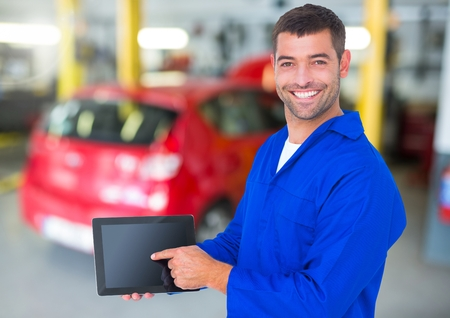 デジタル タブレットを保持している幸せな自動車整備工の肖像画