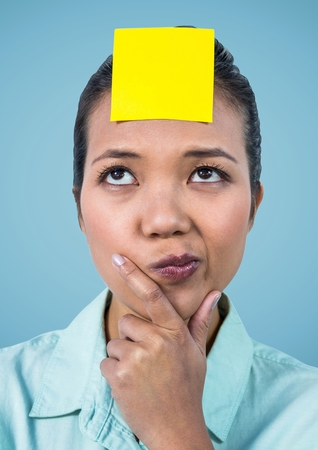 Close-up of confused woman with blank yellow sticky note on her forehead
