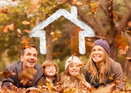 Digital composition of happy family overlaid with house shape lying on dry leaves in park