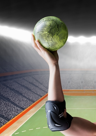 terrain de handball: Composition numérique d'une main tenant le handball dans le stade Banque d'images