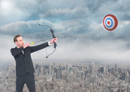 handholding: Digital composition of businessman aiming with bow and arrow at target in sky over cityscape