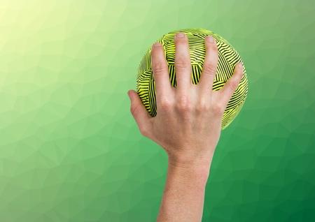 manos unidas: Digital imagen compuesta de atleta mano que sostiene la bola contra el fondo verde de textura Foto de archivo