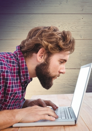 koncentrovaný: Soustředěný muž pomocí přenosného počítače na stole před dřevěné pozadí